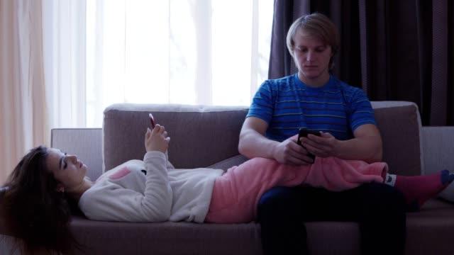 familia-la-tecnología-dificultades-de-relación-y-concepto-de-la-gente---pareja-con-smartphones-enviar-mensajes-de-texto-en-casa