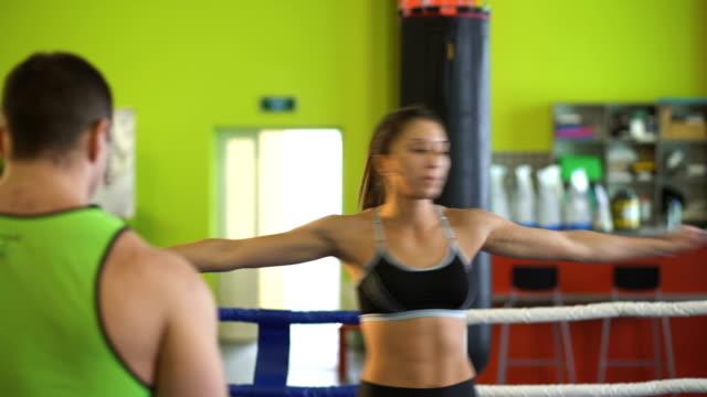 Entrenamiento-de-la-mujer-joven-pre-partido-de-calentamiento-en-el-ring-de-boxeo-con-Het-Trainer-