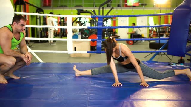Joven-entrenadora-pre-partido-de-calentamiento-en-el-ring-de-boxeo-con-su-entrenador-
