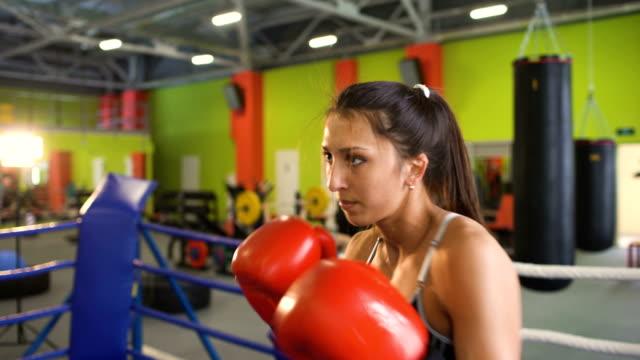 El-entrenamiento-de-la-mujer-joven-boxeador-pre-partido-de-calentamiento-en-el-ring-de-boxeo-con-su-entrenador