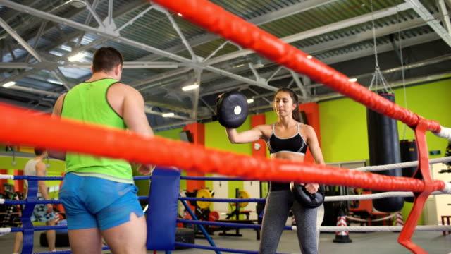 Entrenador-de-Kickboxing-hombre-entrenar-con-la-mujer-joven-en-anillo-de-boxeo
