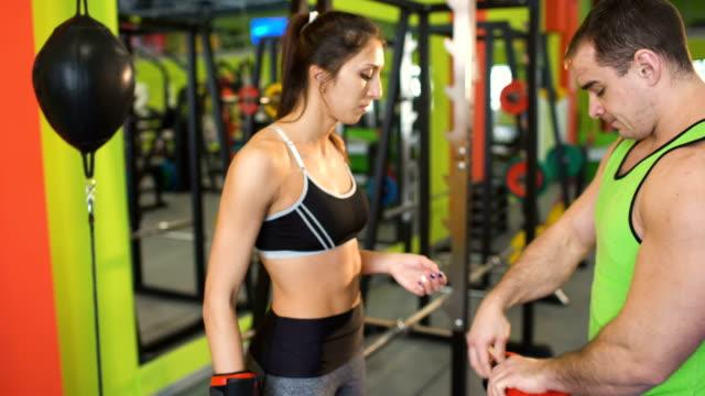 El-hombre-entrenador-de-boxeo-ayuda-a-vestir-los-guantes-de-boxeo-a-la-mujer-joven-en-el-Club-de-fitness