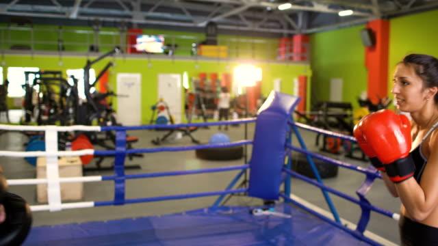 Entrenamiento-de-kickboxer-de-mujer-joven-pre-partido-de-calentamiento-en-el-ring-de-boxeo-con-su-entrenador