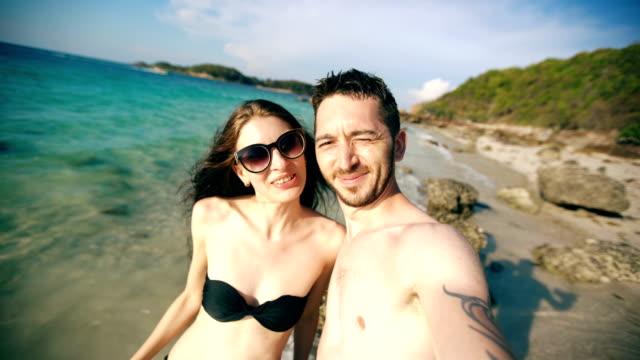 Joven-pareja-feliz-hablando-con-amigos-a-través-de-Internet-utilizando-el-teléfono-inteligente-en-la-playa-oceánica