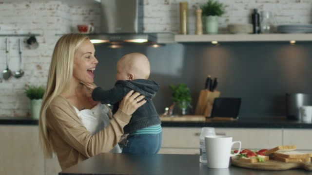Young-Mother-Plays-with-Her-Beautiful-Baby-while-Standing-on-the-Kitchen-In-Slow-Motion-
