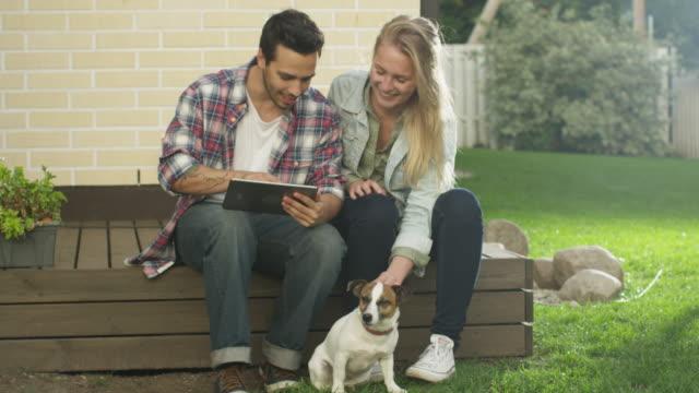 Junge-Mann-und-Frau-mittels-Touchscreen-Tablet-Computer-zusammen-sind-sie-auf-Hinterhof-Bright-Sommertag-