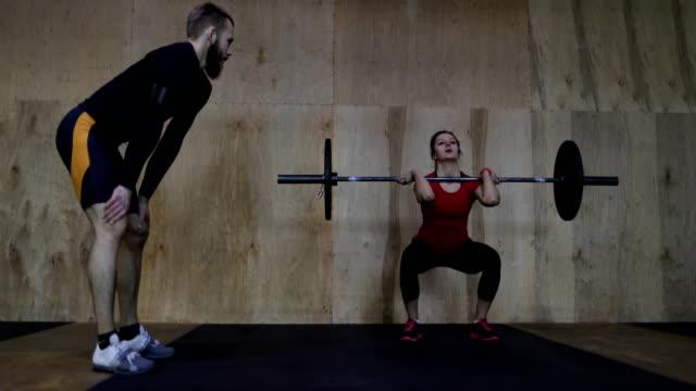 Mujer-atlética-levantamiento-de-pesas-trabajando-con-Entrenador-Personal-en-gimnasio