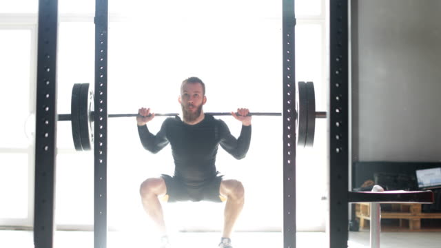 Young-Man-Exercising-Doing-Weighted-Squats-On-Smith-Machine-During-Workout-Training-At-Gym