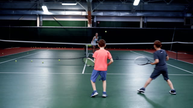 A-female-trainer-in-a-sports-suit-teaches-playing-tennis-in-two-middle-aged-boys-guys-are-bouncing-balls-on-a-tennis-court