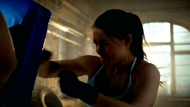 Athletic-Woman-Hits-Punching-Bag-that-Her-Partner/-Trainer-Holds-She-s-Professional-Fighter-and-is-Training-in-a-Gym-