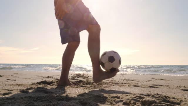Hombre-joven-en-bañador-haciendo-trucos-con-fútbol-en-el-pie-en-la-orilla-del-mar-en-la-playa-de-silueta-al-atardecer