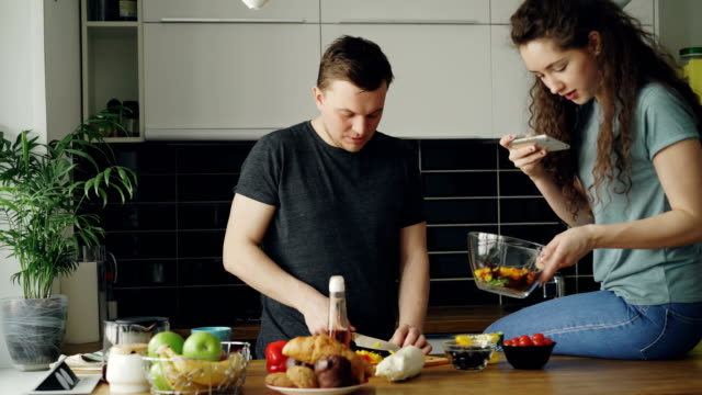 Attractive-young-couple-cooking-and-chatting-happily-in-the-kitchen-at-home-Man-cutting-vegetables-for-salad-and-his-girlfriend-taking-photos-on-smartphone-camera-for-social-media