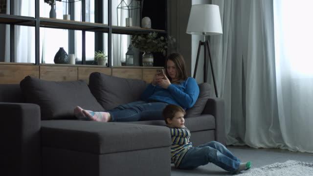 Mother-ignoring-her-little-boy-in-the-bedroom