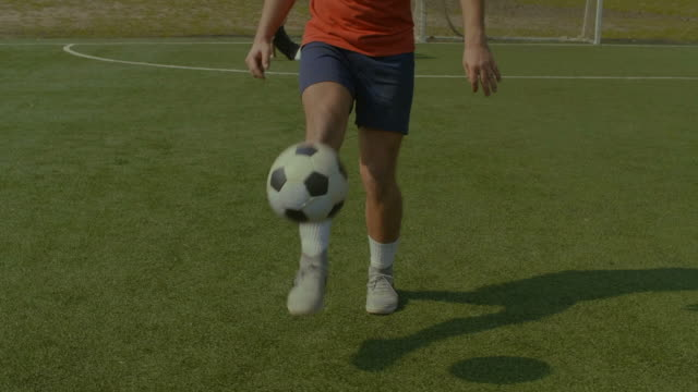 Football-player-juggling-soccer-ball-on-the-pitch