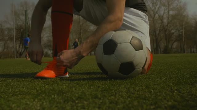 Atar-cordones-de-los-zapatos-en-el-campo-de-fútbol-del-jugador-del-fútbol