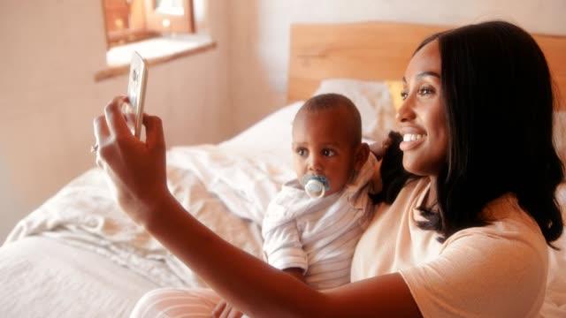 Madre-con-bebé-hijo-video-chat-en-smartphone-en-el-país