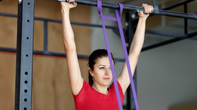 Woman-Hanging-On-Bar-Doing-Pulling-Up-Exercise-During-Workout-Training-At-Gym
