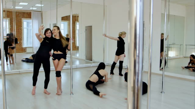 Cute-and-happy-pole-dancers-taking-a-break-from-practice-and-having-fun