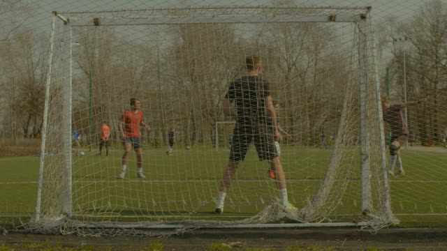 Striker-taking-a-shot-on-goal-during-football-match