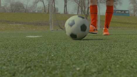Football-player-kicking-soccer-ball-on-the-field