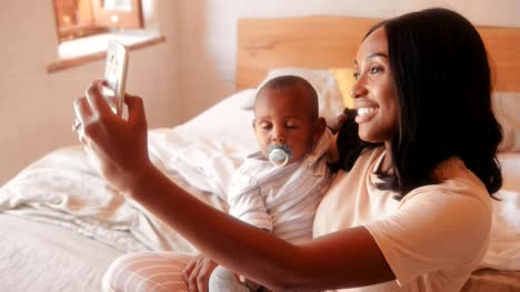 Mother-with-baby-son-video-chatting-on-smartphone-at-home