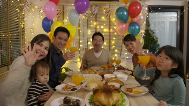 Familienglück-Asian-video-Anruf-tätigen-und-Weihnachtsessen-zu-Hause-gemeinsam-genießen-