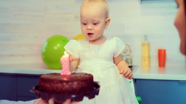 Bebé-está-tratando-de-soplar-la-vela-en-el-pastel-de-cumpleaños
