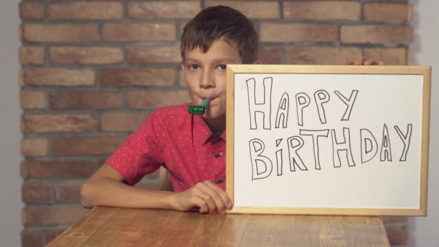 child-sitting-at-the-desk-holding-flipchart-with-lettering-happy-birthday-on-the-background-red-brick-wall