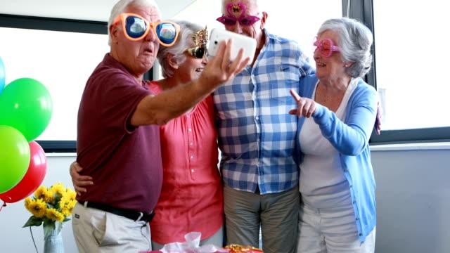 Tercera-edad-tomando-selfie-en-teléfono-móvil-durante-la-fiesta-de-cumpleaños