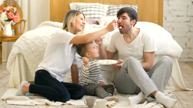 Little-adorable-boy-celebrating-his-birthday-with-father-and-mother-eat-cake-in-bedroom