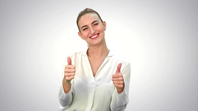 Feliz-mujer-excitada-mostrando-pulgar-de-gesto-de-la-mano-de-aprobación-y-sonriendo-sobre-fondo-blanco