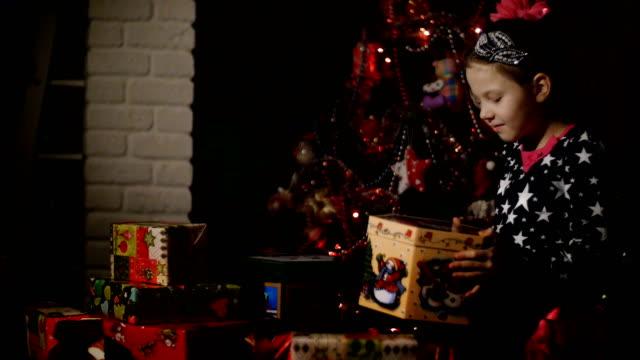 En-el-crepúsculo-de-la-noche-una-chica-muy-rubia-y-con-un-lazo-rosa-en-el-pelo-en-un-hermoso-vestido-admira-regalos-de-Navidad-se-abre-un-cuadro-grande-llenando-la-habitación-con-un-resplandor-mágico-ella-es-feliz-alegre-En-el-fondo-es-un-árbol-de-Navidad-en-color