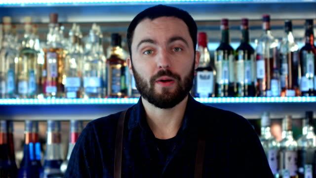 Positive-bartender-talking-to-a-camera-at-a-bar-counter