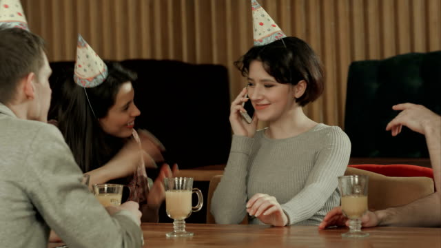 Young-girl-celebrating-birthday-in-cafe-talking-on-cell-phone