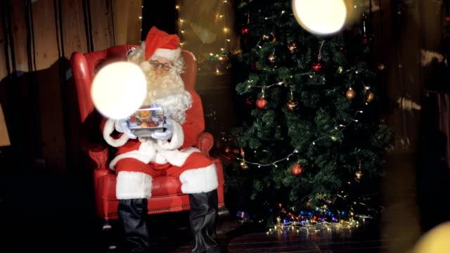 Santa-Claus-put-a-gift-box-under-Christmas-tree-
