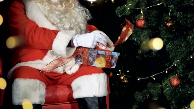 Santa-Claus-tying-ribbons-on-a-gift-box-Christmas-Eve-concept-