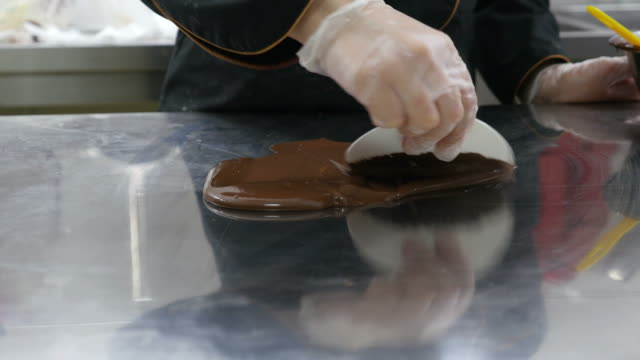 A-confectioner-spreading-chocolate-topping-on-a-table-in-order-to-make-chocolate-decorations