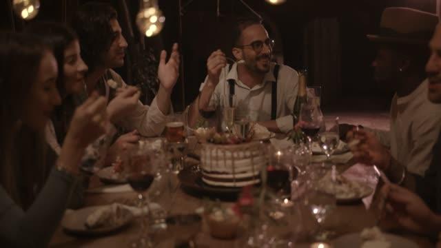 Multi-ethnischen-Freunde-Essen-Gourmet-Geburtstagskuchen-auf-rustikales-Abendessen-party