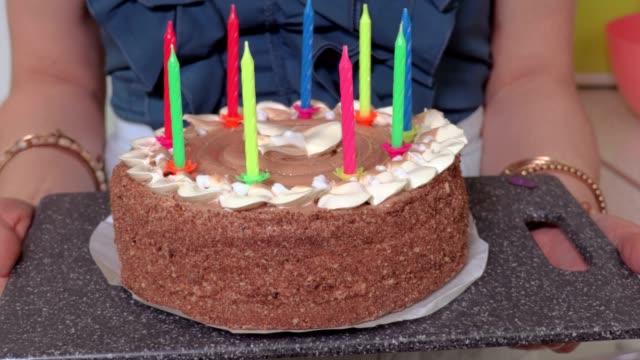Mujer-con-pastel-de-cumpleaños-en-su-casa-en-la-cocina