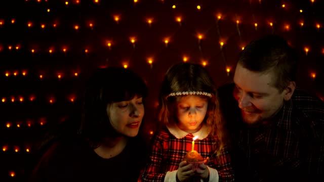 Una-niña-sopla-una-vela-de-un-pastel-festivo-con-su-mamá-y-papá-