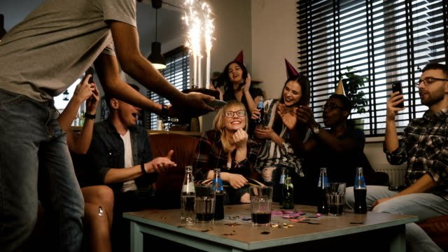 Pretty-girl-celebrates-birthday-with-her-friends-Multi-ethnic-party-with-cake-and-Bengal-light-sparkling-firework-4K