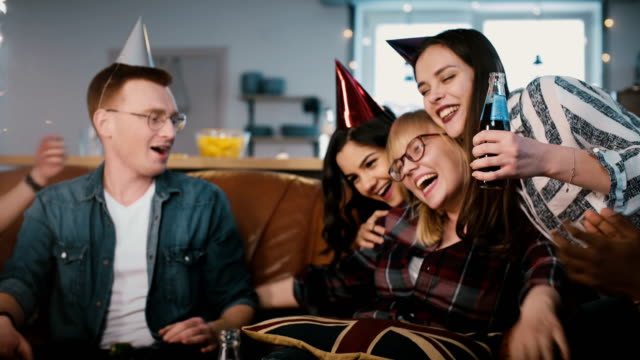 European-woman-hugs-friends-on-her-birthday-party-Happy-multi-ethnic-youth-share-birthday-celebration-together-4K