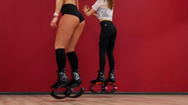 Una-hermosa-chica-en-un-fondo-de-pared-roja-realiza-sentadillas-para-fortalecer-los-músculos-del-muslo-Entrenamiento-de-glúteos-músculos-en-botas-sobre-resortes-Zapatos-de-los-deportes-Kangoo-salta
