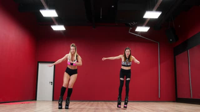 Two-beautiful-sports-girls-perform-an-active-fat-burning-workout-jumping-like-a-kangaroo-in-special-fitness-shoes-Cardio-workout-for-endurance-kango-jump