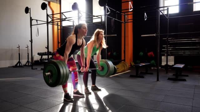 Equipo-de-dos-mujeres-de-fitness-hacer-ejercicio-de-peso-muerto-en-gimnasio