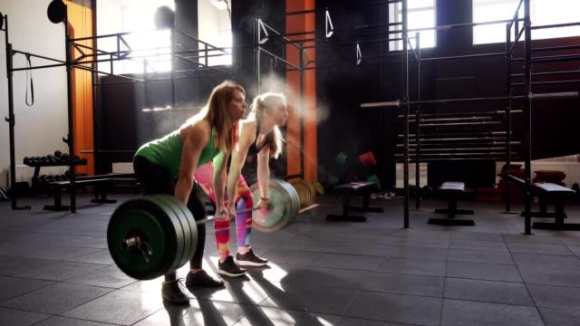 Equipo-de-dos-mujeres-de-gimnasio-haciendo-ejercicios-de-peso-muerto-dando-cinco-alta-y-ganar