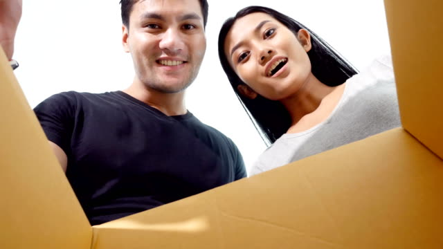 Man-and-Woman-open-the-box-with-happy-emotion-together-at-home-Man-surprise-he-wife-and-give-present-to-her-at-home-People-lifestyle-concept-4K-Resolution-