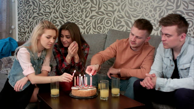 Teen-boy-lighting-a-birthday-candle-on-cake-with-friends-at-home