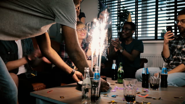 Multiethnic-friends-congratulate-Caucasian-shy-birthday-girl-with-sparkling-firework-cake-at-surprise-party-slow-motion