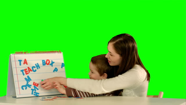 Mother-and-son-make-word-Mama-on-the-desk-on-a-Green-Screen